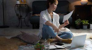 mujer sobre la alfombra trabajando para ganar dinero desde casa